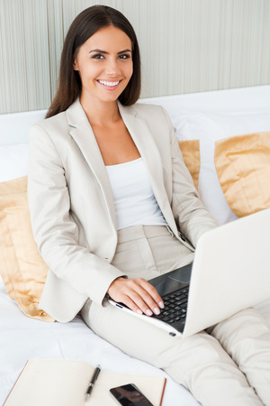 Staying in touch with office. Top view of confident young businesswoman in suit working on laptop and smiling while sitting in bed at the hotel room photo