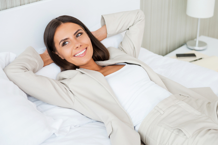 Relaxing in hotel room. Top view of beautiful young businesswoman in suit holding hands behind head and smiling while lying in bed at the hotel room photo