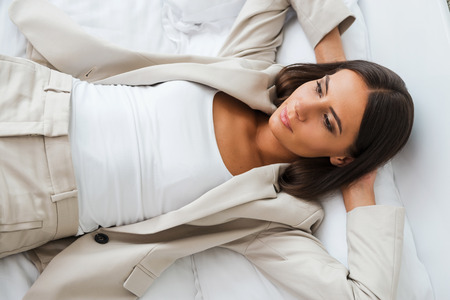 keeping room: Tired after hard working day. Top view of beautiful young businesswoman in suit holding hands behind head and keeping eyes closed while lying in bed at the hotel room  Stock Photo