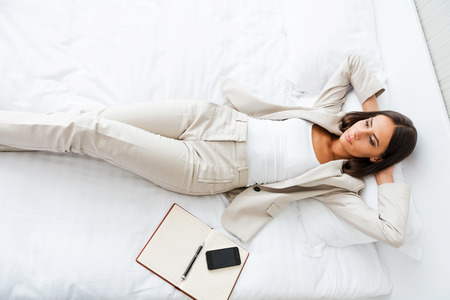 hotel worker: Relaxing in hotel room. Top view of beautiful young businesswoman in suit holding hands behind head and keeping  while lying in bed at the hotel room