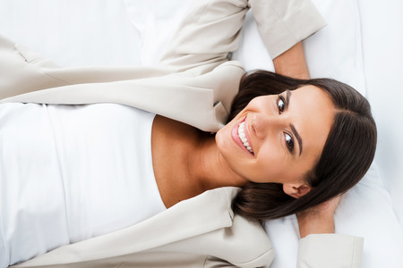 Taking time to relax. Top view of beautiful young businesswoman in suit holding hands behind head and smiling while lying in bed at the hotel room  photo
