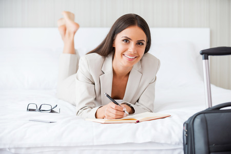 Making some urgent notes. Beautiful young businesswoman in suit writing something in her note pad and smiling while lying in the bed at the hotel room  photo