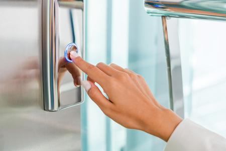 pushing the button: Al pulsar el bot�n. Primer plano de la mano femenina bot�n del ascensor empujando