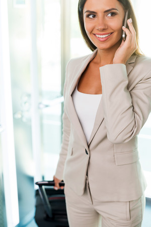 Executive on the go. Beautiful young businesswoman in suit talking on the mobile phone and smiling while getting out of elevator photo