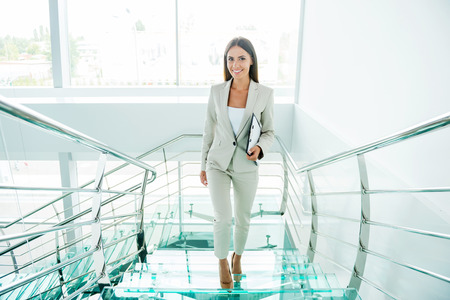 business attire: Young and successful. Beautiful young businesswoman in formalwear moving up by staircase and smiling Stock Photo