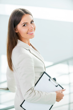 looking over shoulder: Young and successful businesswoman. Rear view of beautiful young smiling businesswoman in formalwear walking by staircase and looking over shoulder