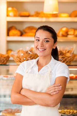 bakery shop: Only fresh pastry for our customers. Beautiful young woman in apron keeping arms crossed while standing in bakery shop