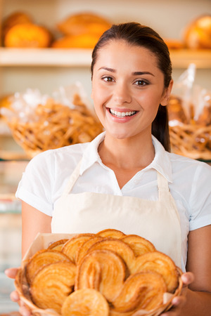 freshest: The freshest bakery for our customers. Beautiful young woman in apron holding basket with baked goods while standing in bakery shop