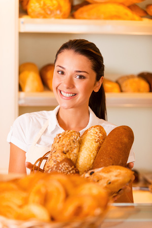 selling service smile: Only the best and fresh bakery. Beautiful young woman in apron holding basket with baked goods while standing in bakery shop Stock Photo