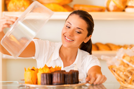 freshest: The freshest bakery for our customers. Beautiful young woman in apron carrying plate with fresh cookies and smiling while standing in bakery shop Stock Photo