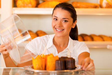 bakery shop: Try this! Attractive young woman in apron carrying plate with fresh cookies and smiling while standing in bakery shop Stock Photo