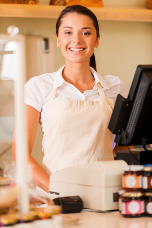 Cheerful cashier. Beautiful young female cashier in apron standing near cash register and smiling  Banque d'images
