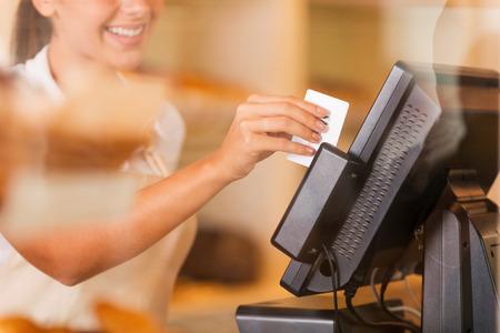 stores: Kassier op het werk. Mooie jonge vrouwelijke kassier swipes een plastic kaart door een machine
