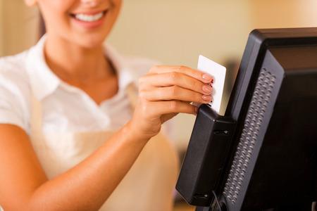 maquina registradora: Cajero en el trabajo. Close-up de la hermosa mujer joven cajero desliza una tarjeta de pl�stico a trav�s de una m�quina