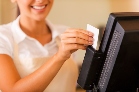 Cashier at work. Close-up of beautiful young female cashier swipes a plastic card through a machine  photo