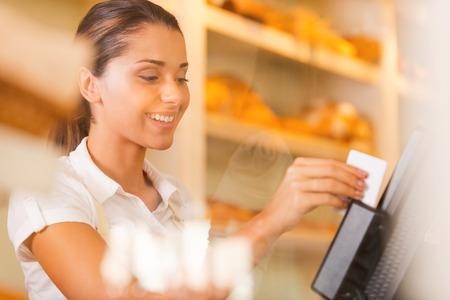 tarjeta de credito: Cajero en el trabajo. Cajero hembra joven atractiva desliza una tarjeta de pl�stico a trav�s de una m�quina y sonriendo