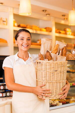 freshest: The freshest bread for our customers. Beautiful young woman in apron holding basket with bread and smiling while standing in bakery shop