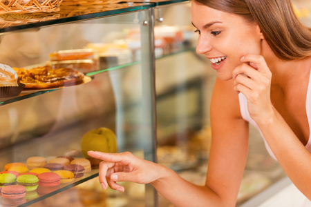 bakery store: I want them all! Beautiful young woman choosing cake in candy shop  Stock Photo