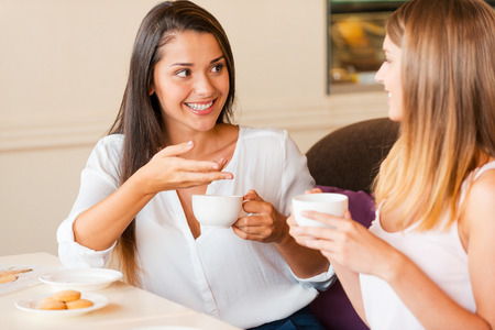 two women talking: We love spending time together. Two beautiful young women drinking coffee and talking while sitting in coffee shop together Stock Photo