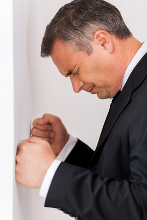 distraught: Depressed businessman. Side view of depressed mature man in shirt and tie leaning at the wall and keeping eyes closed