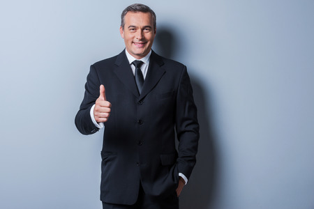 Thumb up for success! Cheerful mature man in formalwear showing his thumb up and smiling while standing against grey background photo