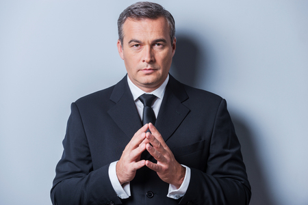 Confident business expert. Confident mature man in formalwear holding hands clasped and looking at camera while standing against grey background