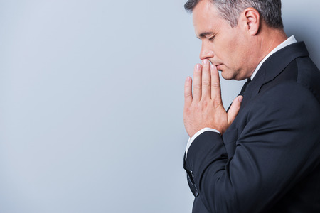 near side: Praying for success. Side view of concentrated mature man in formalwear holding hands clasped near face and keeping eyes closed while standing against grey background Stock Photo