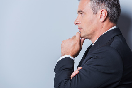Lost in business thoughts. Side view of thoughtful mature man in formalwear holding hand on chin and looking away while standing against grey background photo