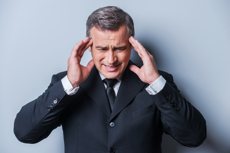 Too stressful day. Frustrated mature man in formalwear touching head with fingers and keeping eyes closed while standing against grey background photo