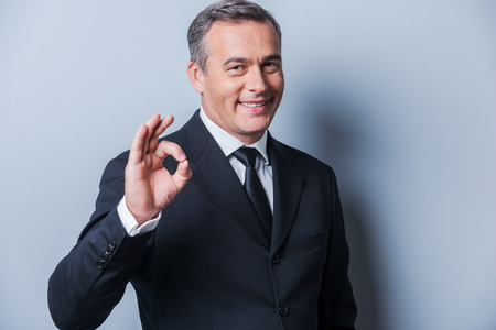 Everything is OK! Cheerful mature man in formalwear gesturing OK sign and smiling while standing against grey background