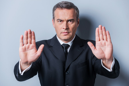 rejection: Stop it! Serious mature man in formalwear showing his palms and looking at camera while standing against grey background