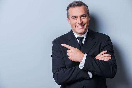 Reclame voor uw product. Vrolijke volwassen man in formalwear kijken naar de camera en lacht terwijl wijst weg en zich tegen grijze achtergrond Stockfoto