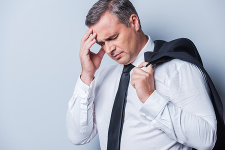 Depressed businessman. Frustrated mature man in formalwear touching head with hand and keeping eyes closed while standing against grey background photo