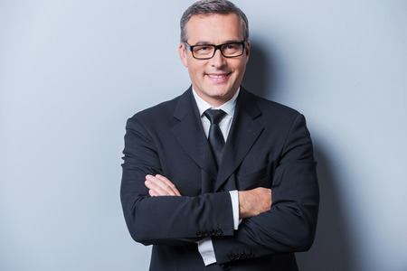 Confident and successful. Portrait of confident mature man in formalwear and eyeglasses looking at camera and smiling while standing against grey background