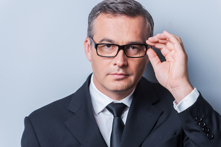 serious businessman: Business expert. Portrait of confident mature man in formalwear adjusting his eyeglasses and looking at camera  while standing against grey background Stock Photo