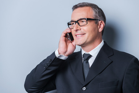 toothy smile: Good business talk. Portrait of confident mature man in formalwear talking on the mobile phone and smiling while standing against grey background