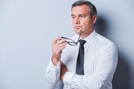 reflexionando: Perdido en pensamientos de negocio. Hombre maduro pensativo en ropa formal la celebraci�n de anteojos y mirando a otro lado mientras est� de pie contra el fondo gris