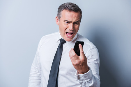 one senior man only: Angry businessman. Furious mature man in shirt and tie holding mobile phone and shouting at it while standing against grey background