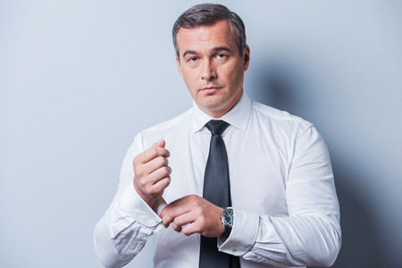 his shirt sleeves: Making business look good. Confident mature man in shirt and tie adjusting his sleeves and looking at camera  while standing against grey background