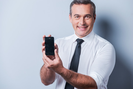 brand new: Presenting brand new smartphone. Confident mature man in shirt and tie showing his new mobile phone and smiling while standing against grey background