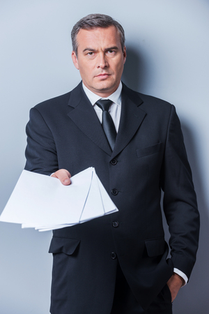 got: I got some paperwork for you. Confident mature man in formalwear stretching out documents and looking at camera while standing against grey background