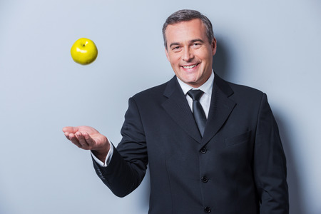 Healthy food for success. Confident mature man in formalwear throwing a green apple up and smiling while standing against grey background photo