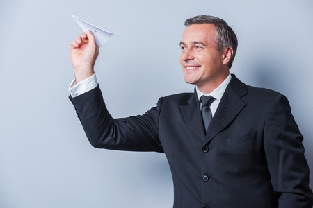 paper airplane: Businessman with paper airplane. Playful mature man in formalwear holding paper airplane and smiling while standing against grey background Stock Photo