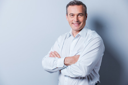 man: Confident mature man. Portrait of confident mature man in shirt looking at camera and smiling while keeping arms crossed and standing against grey background Stock Photo