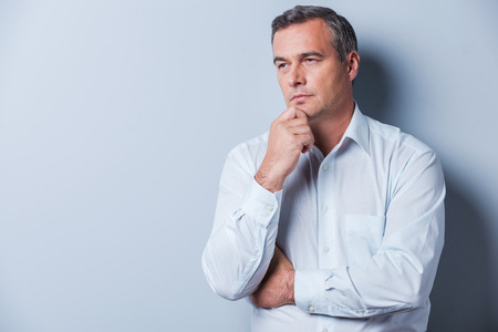 Lost in thoughts. Portrait of thoughtful mature man in shirt holding hand on chin and looking away while standing against grey background Imagens