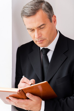 one senior man only: Making urgent notes. Confident mature man in formalwear writing something in note pad while leaning at the wall