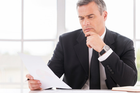 power of thinking: Businessman examining contract. Thoughtful mature man in formalwear holding hand on chin while examining document and sitting at working place