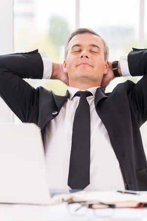 Taking time to relax. Relaxed mature man in formalwear holding hands behind head and keeping eyes closed while sitting at his working place photo