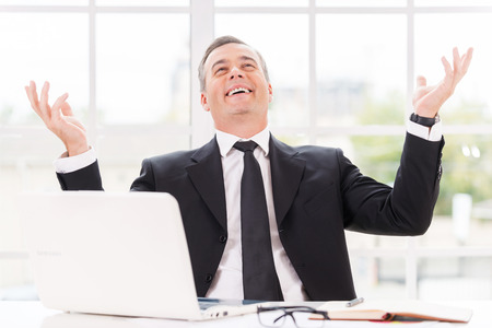 expressing positivity: Confident and successful. Happy mature man in formalwear smiling and gesturing while sitting at his working place Stock Photo