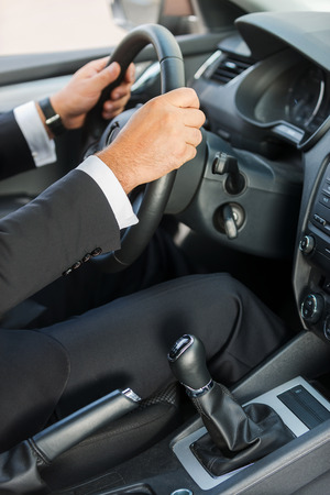 test drive: Man driving a car. Close-up of man in formalwear driving car  Stock Photo